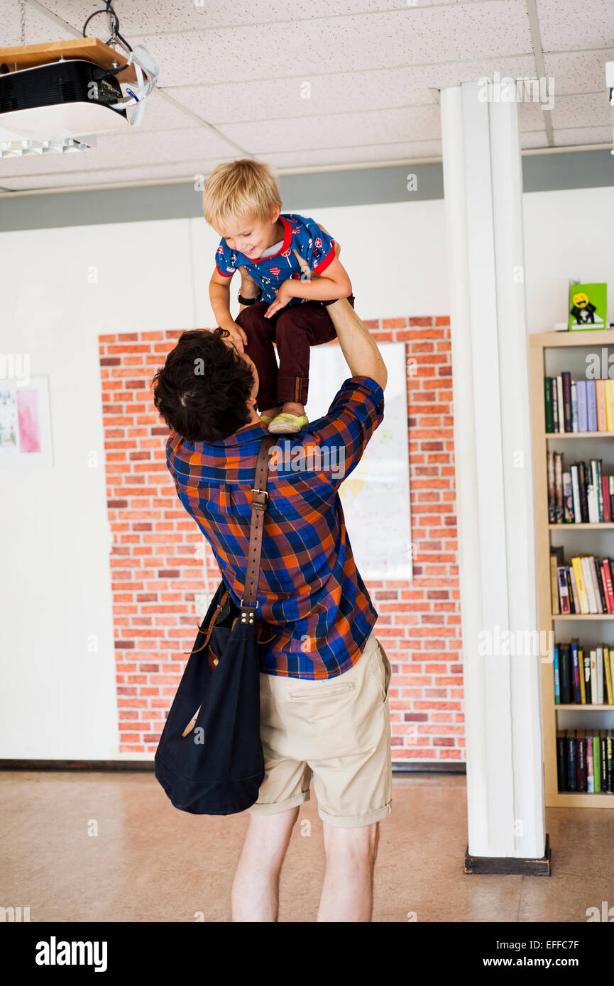 Father lifting son at primary school - Stock Image