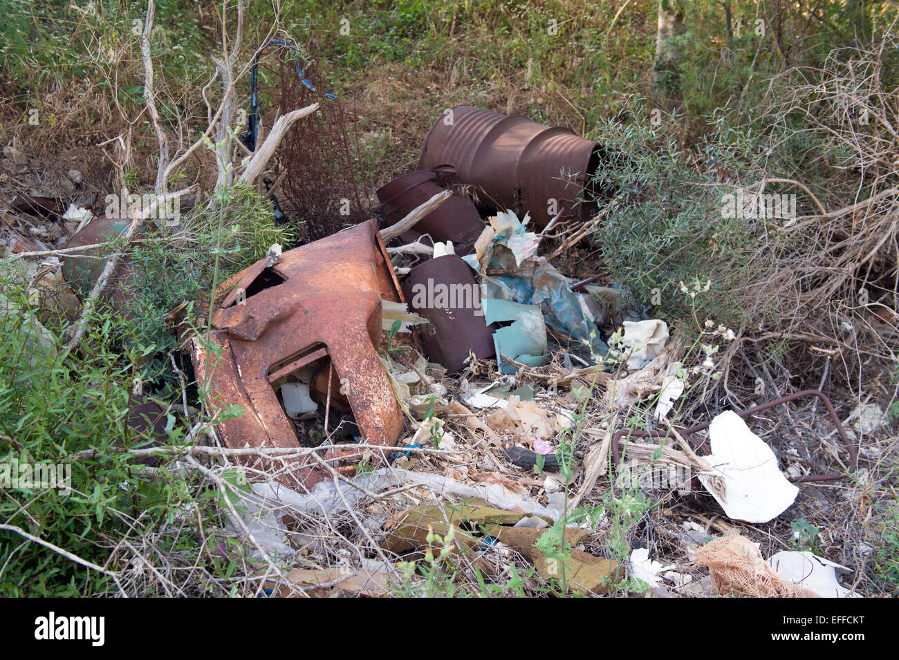 Dumping ground with metal barrels and other garbage - Stock Image