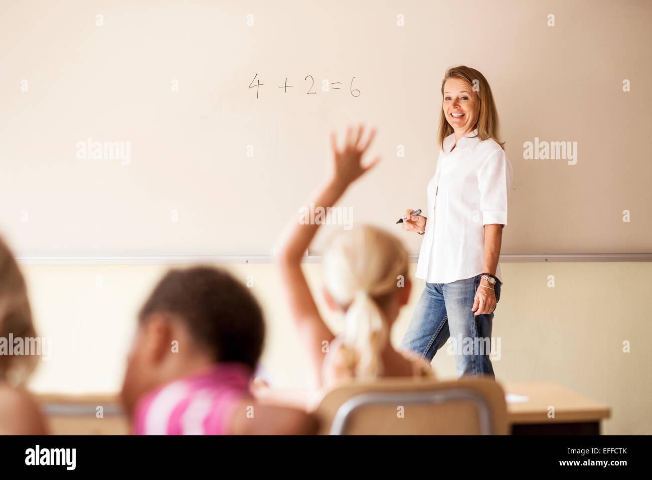 Mature teacher teaching mathematics to children in classroom - Stock Image