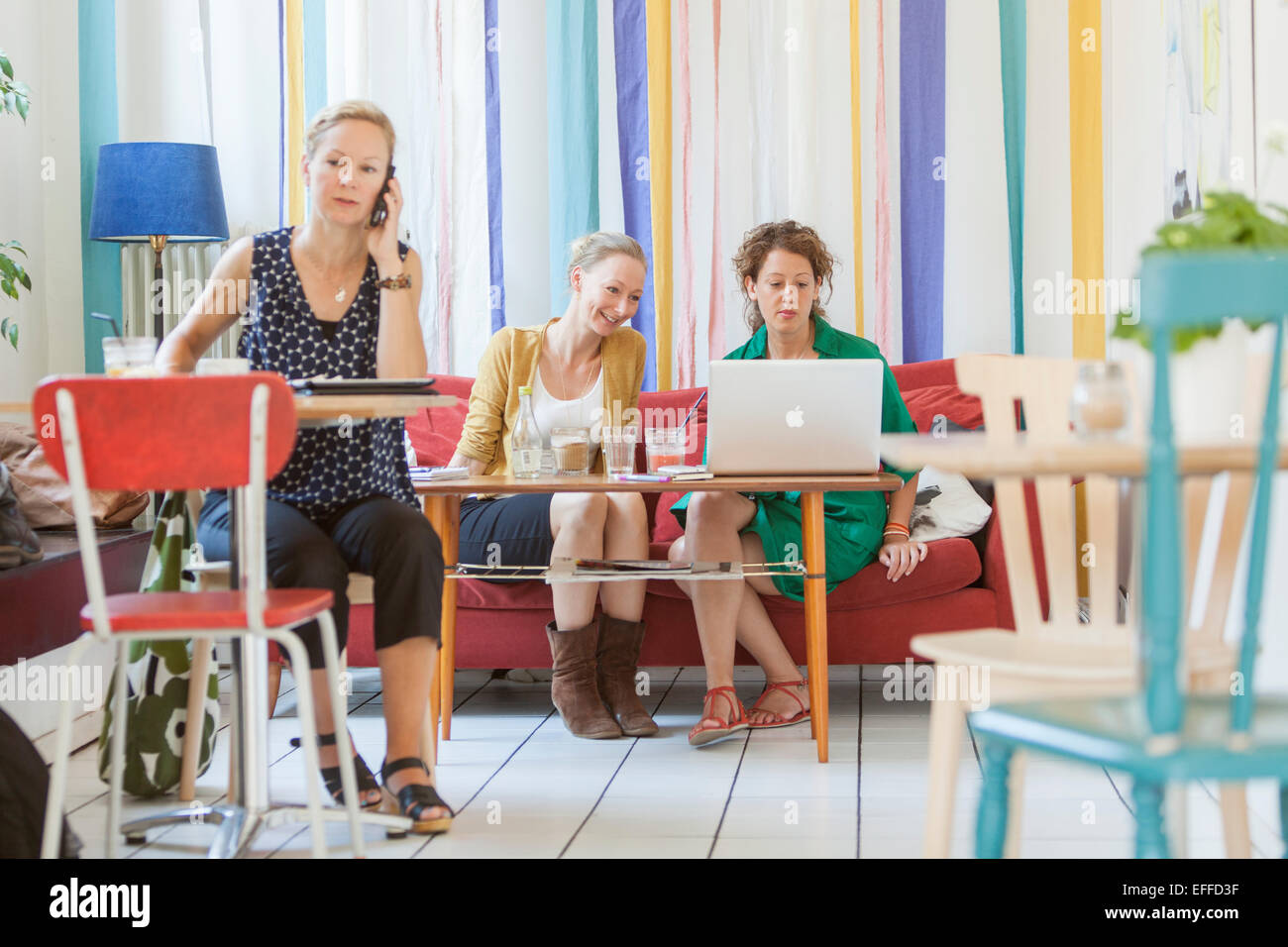 Full length of women using technologies in coffee shop - Stock Image