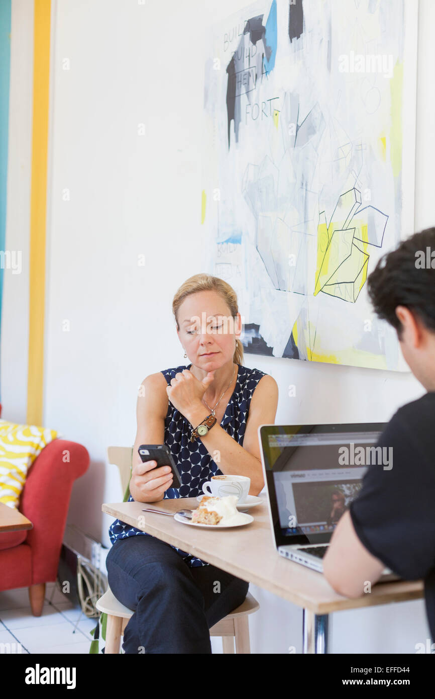 Man and woman using technologies at cafe table - Stock Image