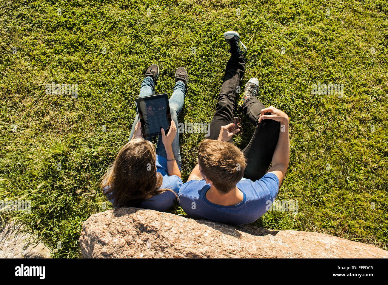 High angle view of couple using digital tablet on grassy landscape - Stock Image