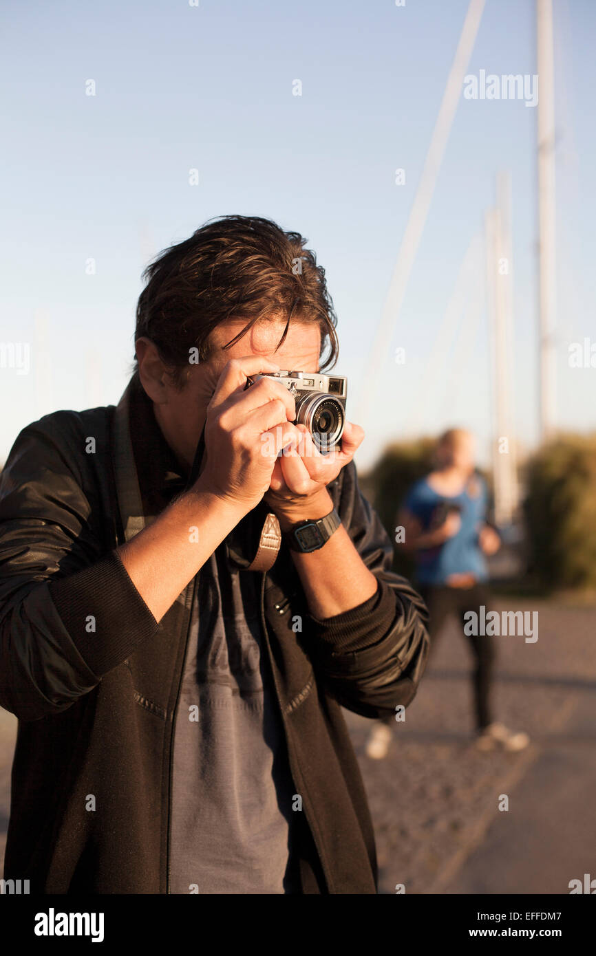 Man photographing through vintage camera on city street against clear sky - Stock Image