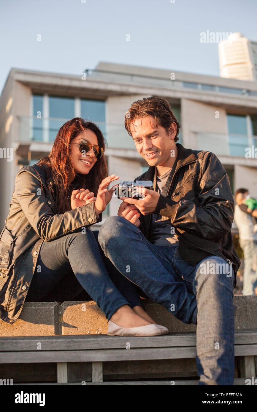 Young couple watching photographs on camera against building - Stock Image