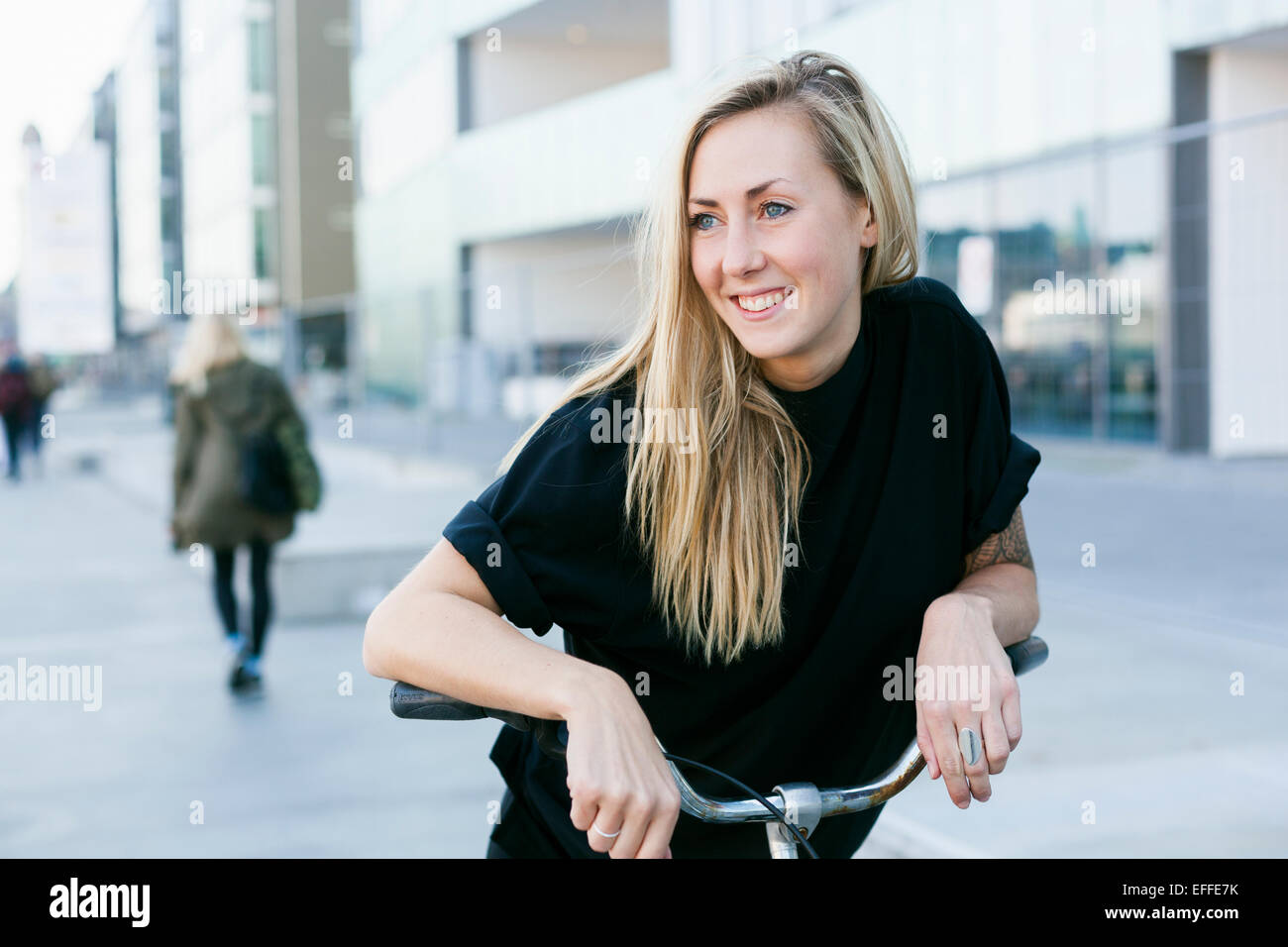 Smiling female college student leaning on bicycle outdoors - Stock Image