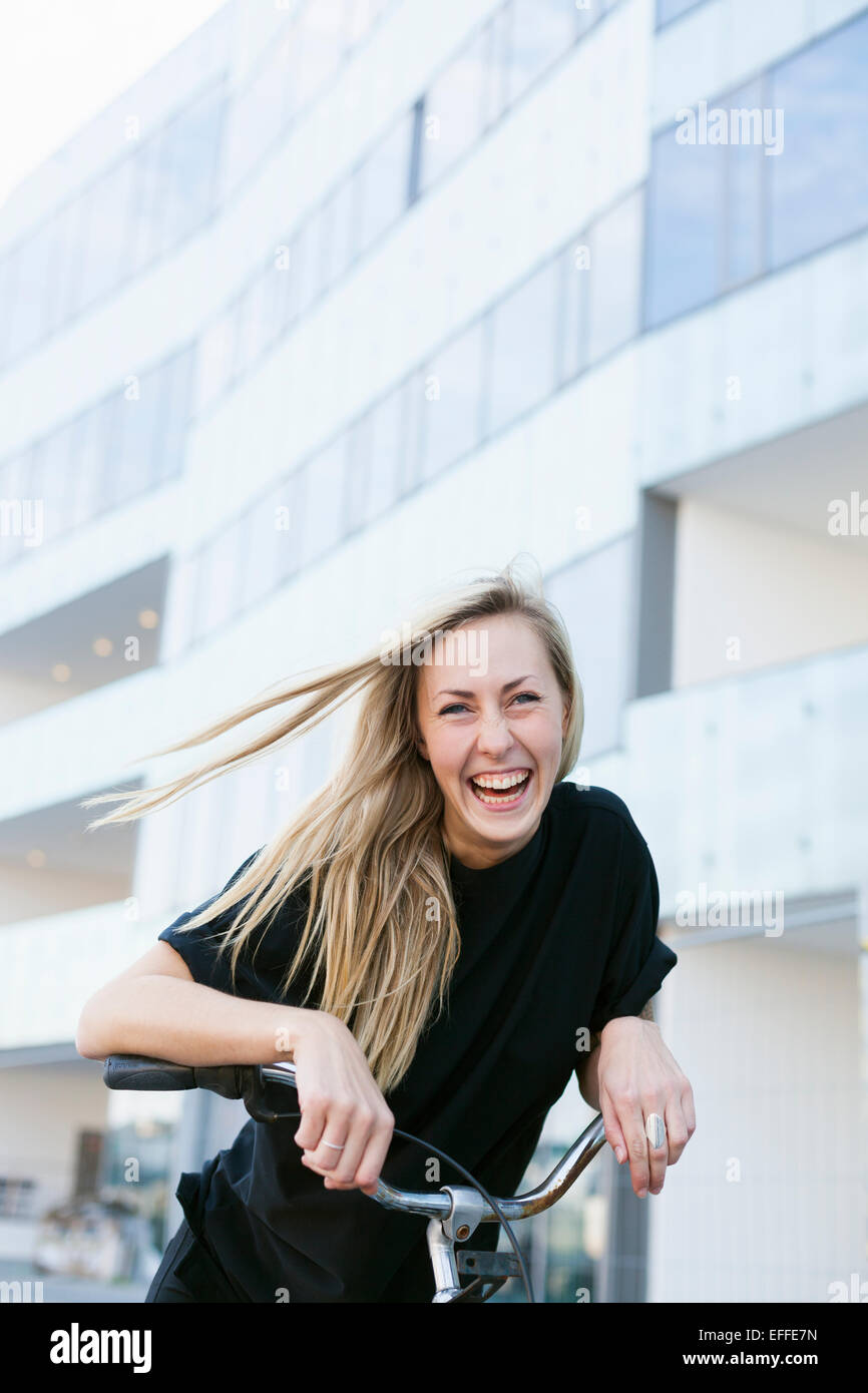 Portrait of cheerful college student with bicycle against building - Stock Image