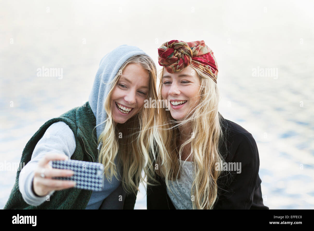 Happy female friends taking selfie through mobile phone against river - Stock Image