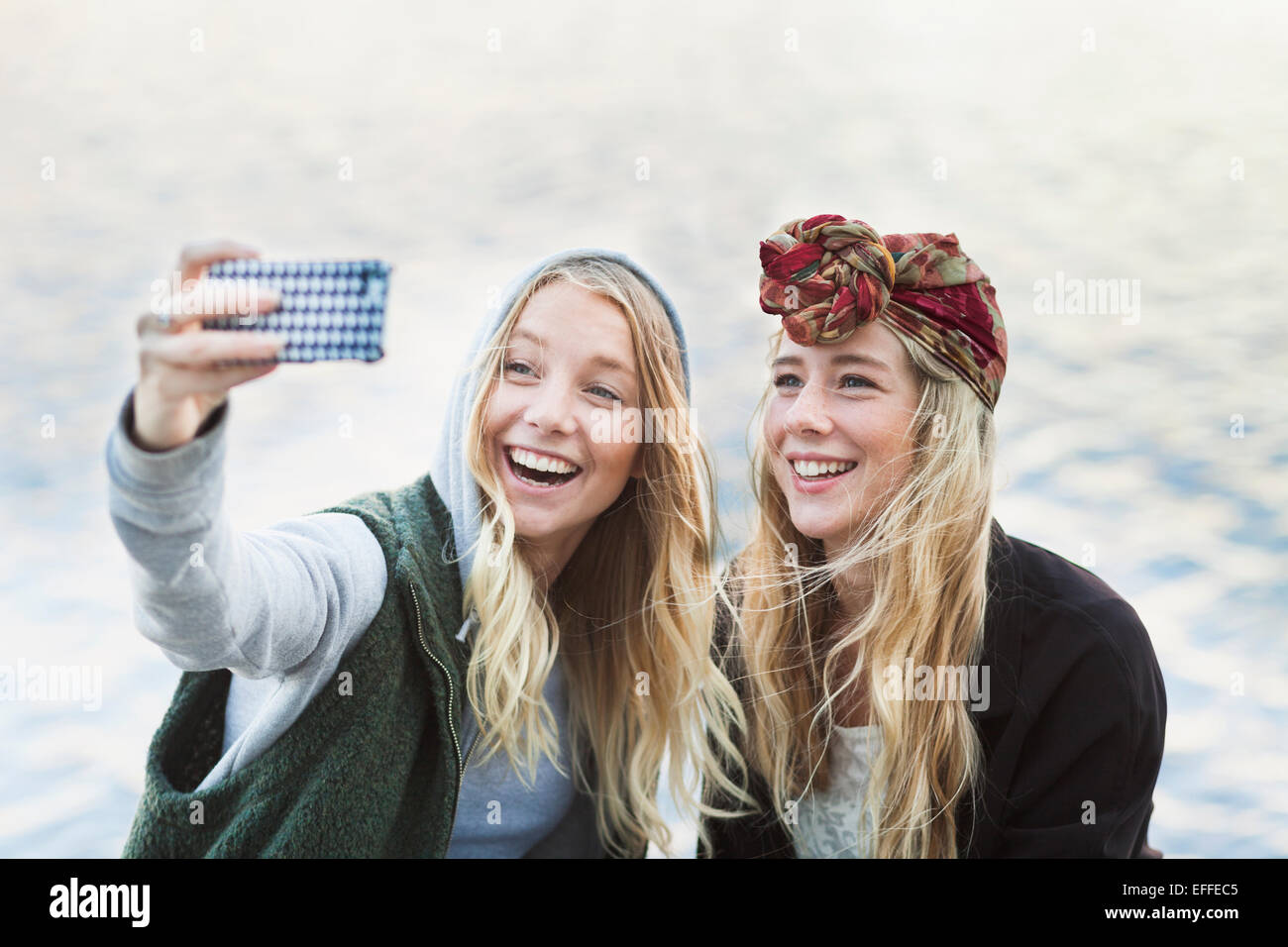 Happy female college students taking selfie through mobile phone against river - Stock Image