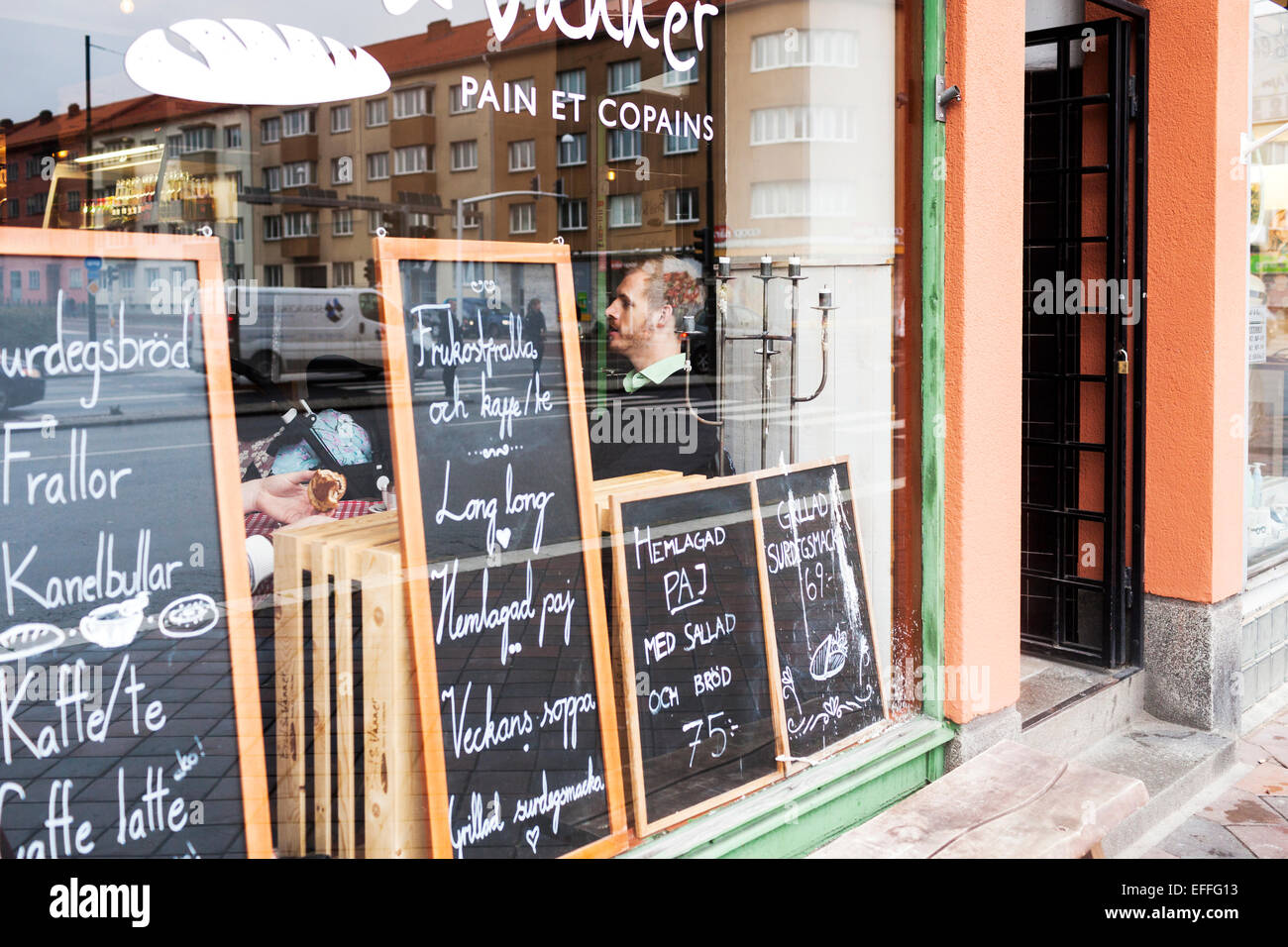 View of man in cafeteria through glass wall with blackboards - Stock Image