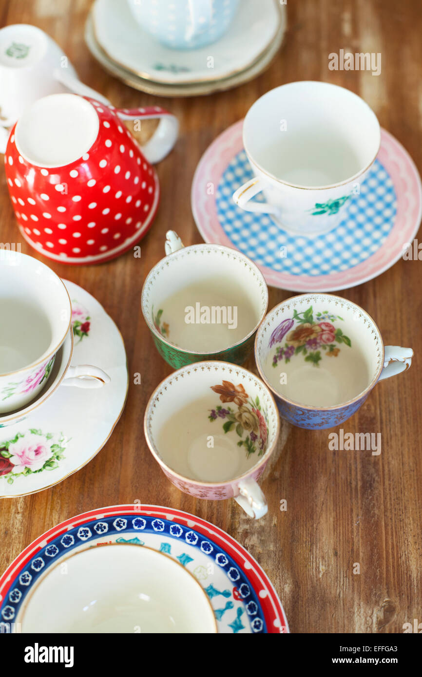 Variety of tea cups and saucers on wooden table - Stock Image
