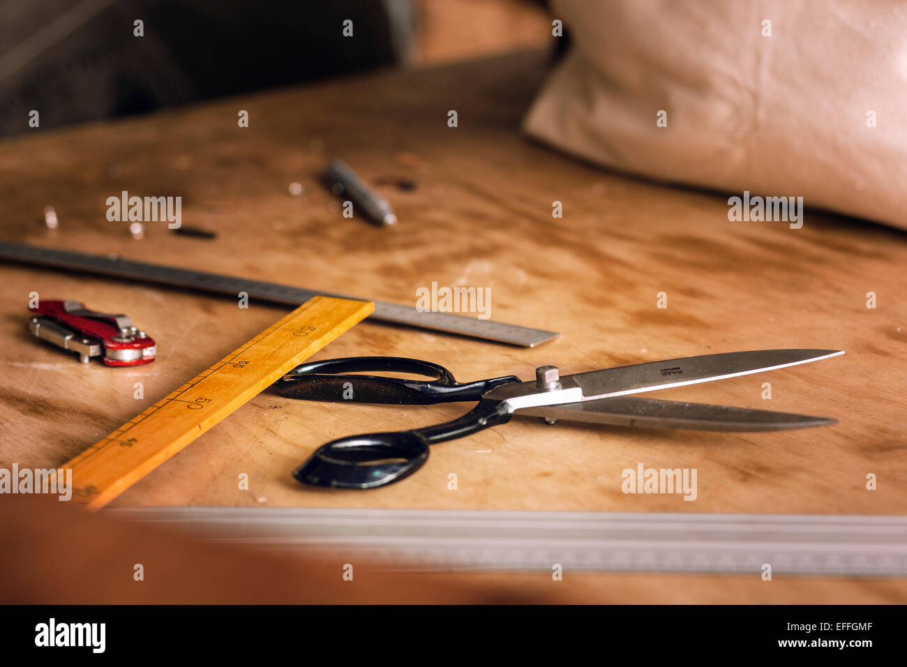 Craft equipment on table at bag manufacturing factory - Stock Image