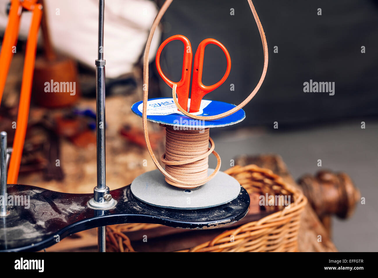 Scissor in rubber spool at bag factory - Stock Image