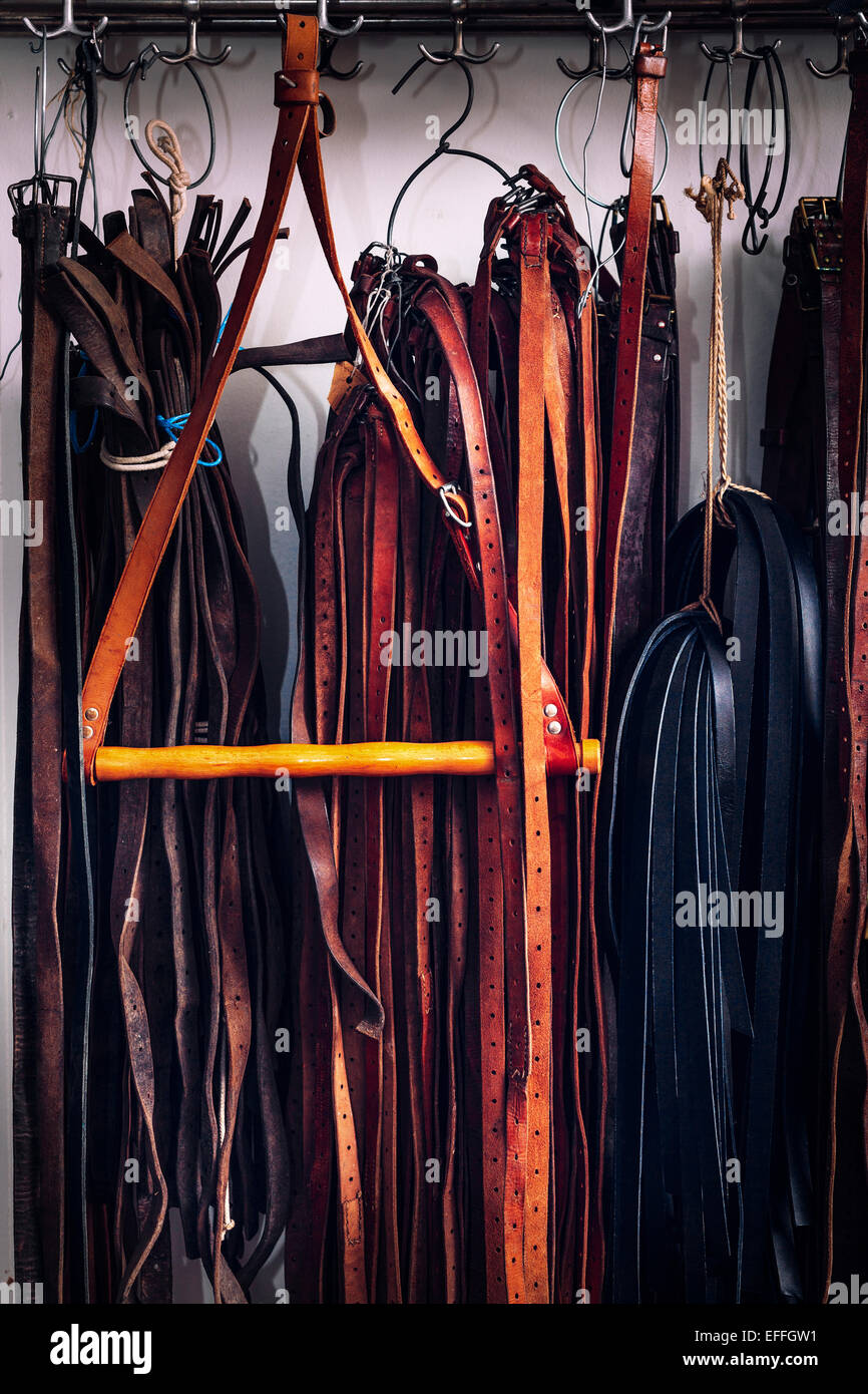 Leather belts hanging in factory - Stock Image