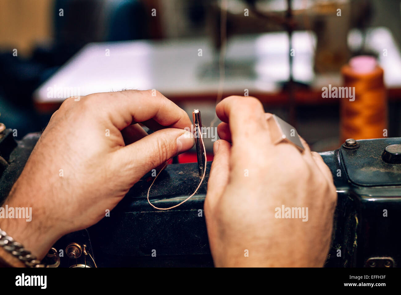 Cropped image of worker's hands inserting thread before manufacturing in factory - Stock Image
