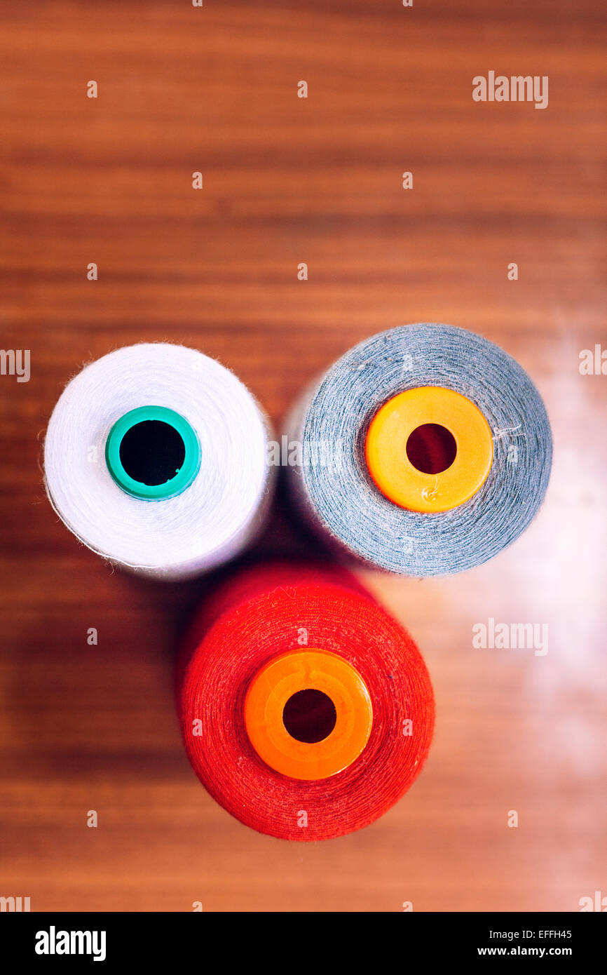 Directly above shot of multicolored thread spools on table at workshop - Stock Image
