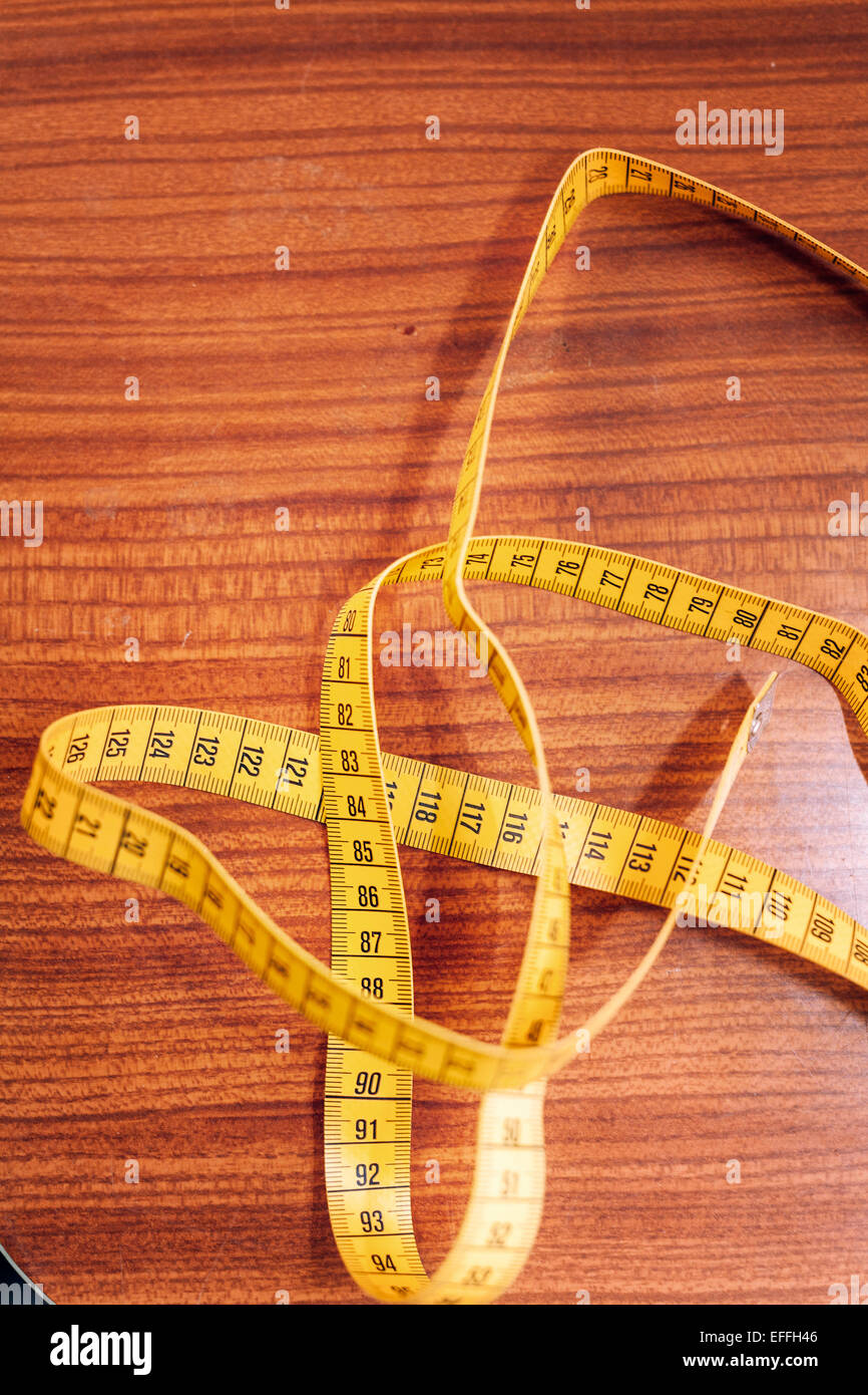 Directly above shot of measure tape on table at workshop - Stock Image