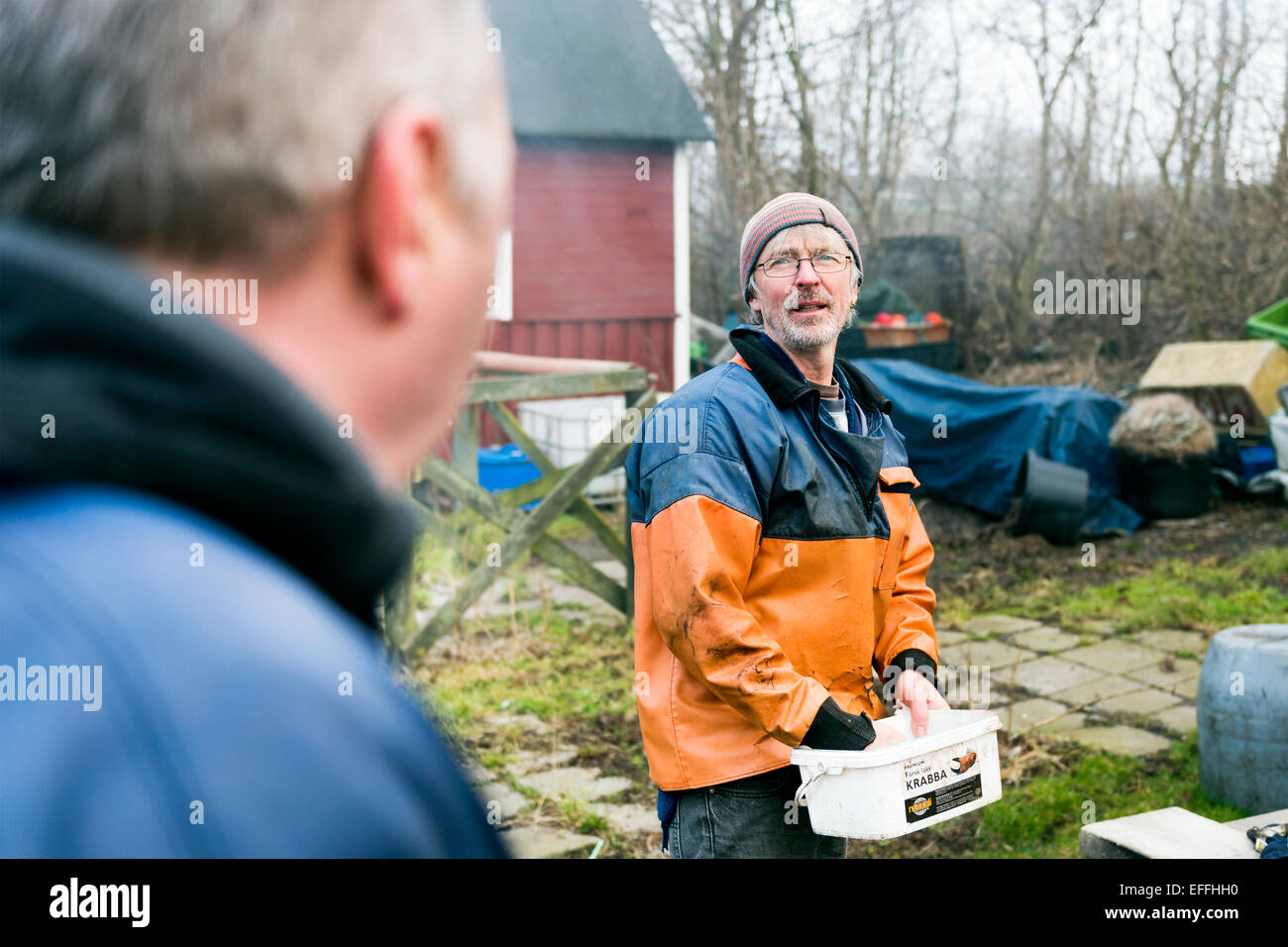 Mature fisherman holding container while talking with colleague outdoors Stock Photo