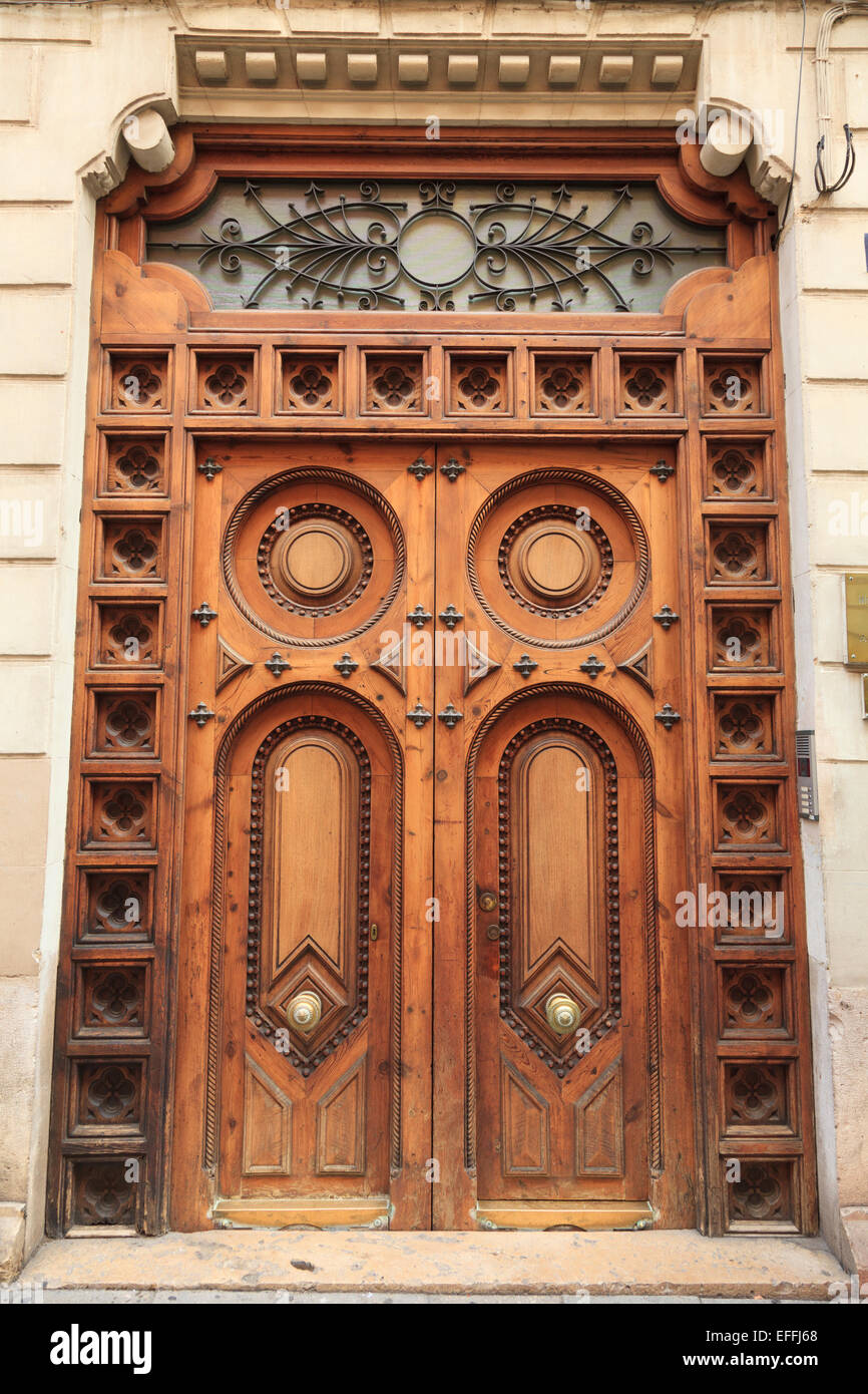Classic ornate substantial carved wooden door on Spanish Building - Stock Image