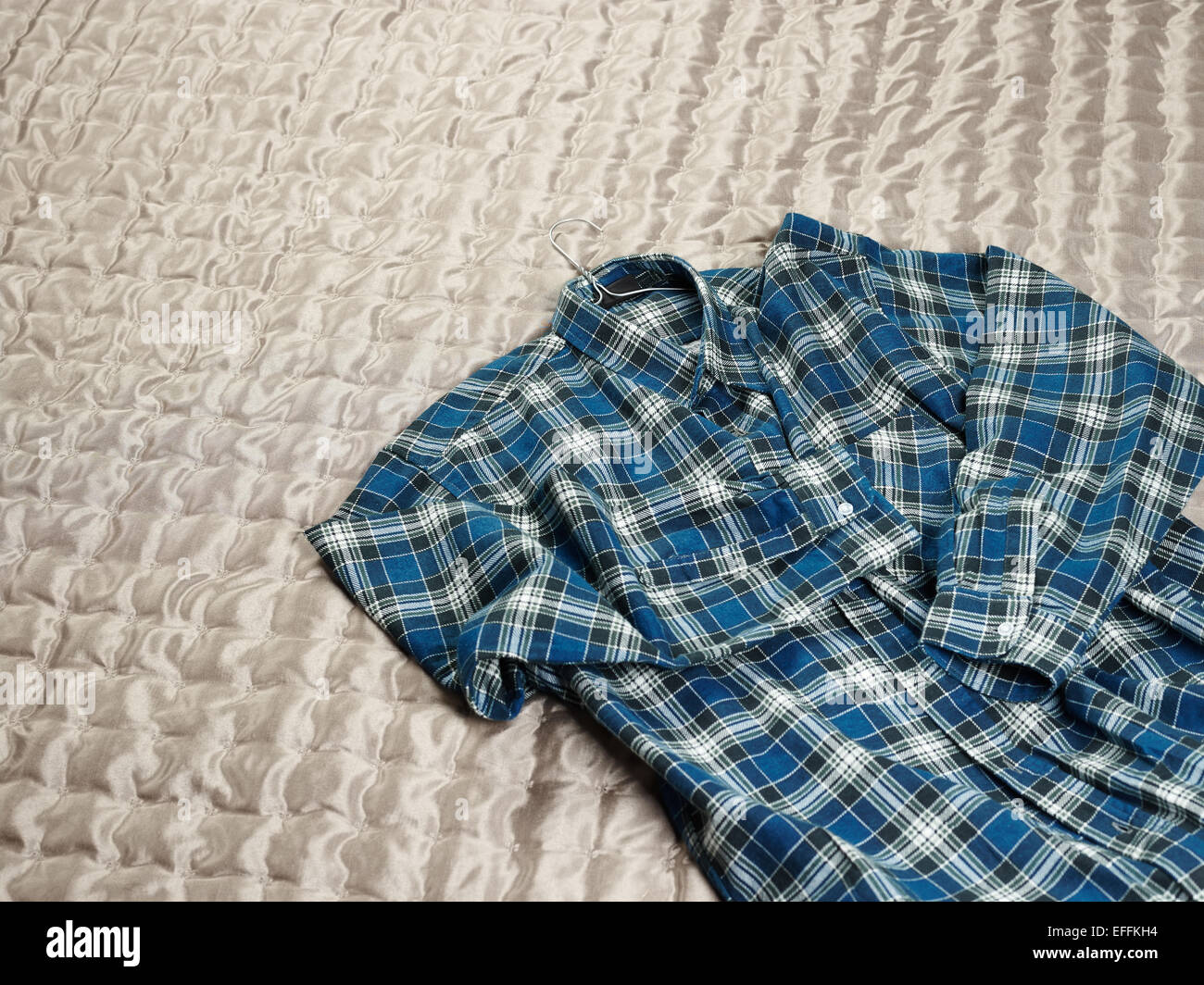 Men's casual checkered shirt on the bed - Stock Image