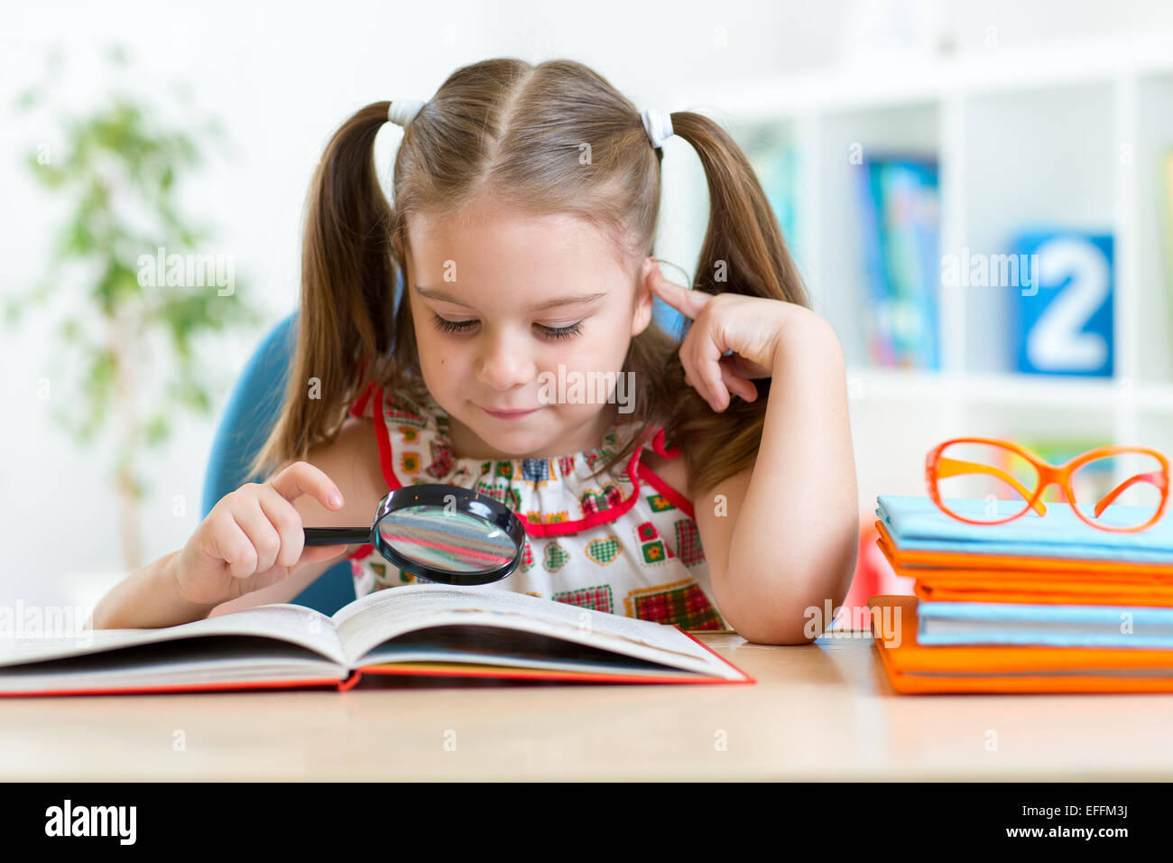 cute kid looking through a magnifying glass with book - Stock Image