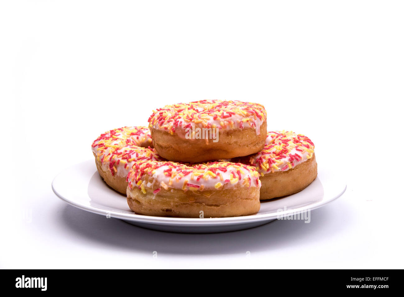 A selection of iced ring donuts on a plate against a white background - Stock Image