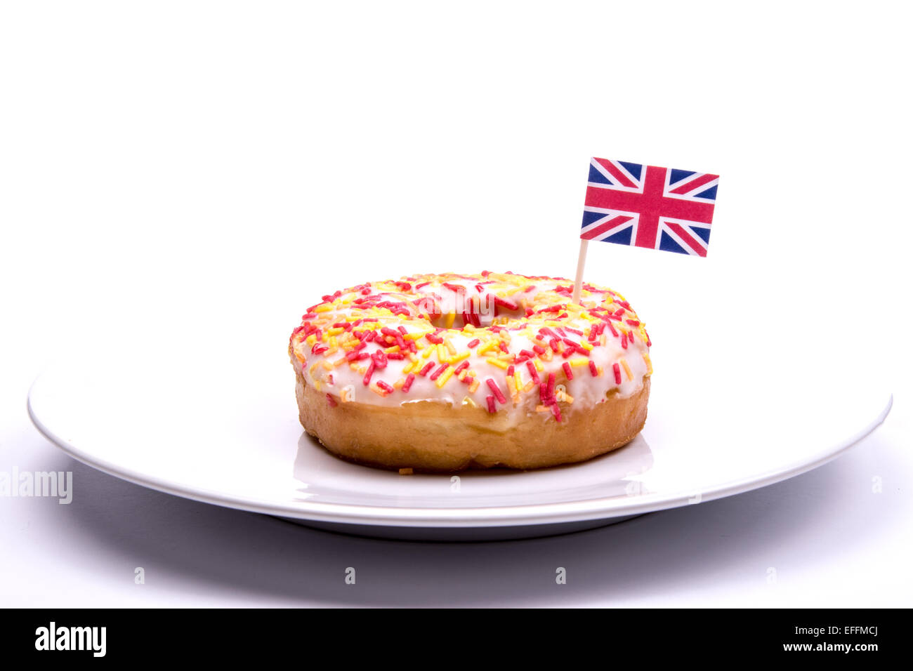 Iced ring donut on a plate with a British Union Jack flag against a white background - Stock Image
