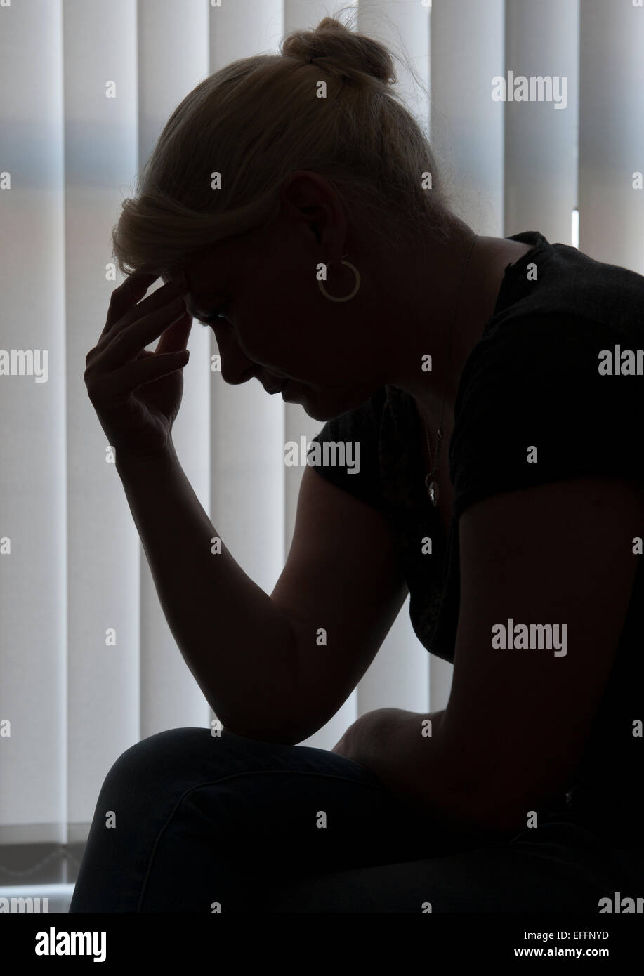A middle aged woman silhouetted against window blinds leans over with her head in her hands. - Stock Image