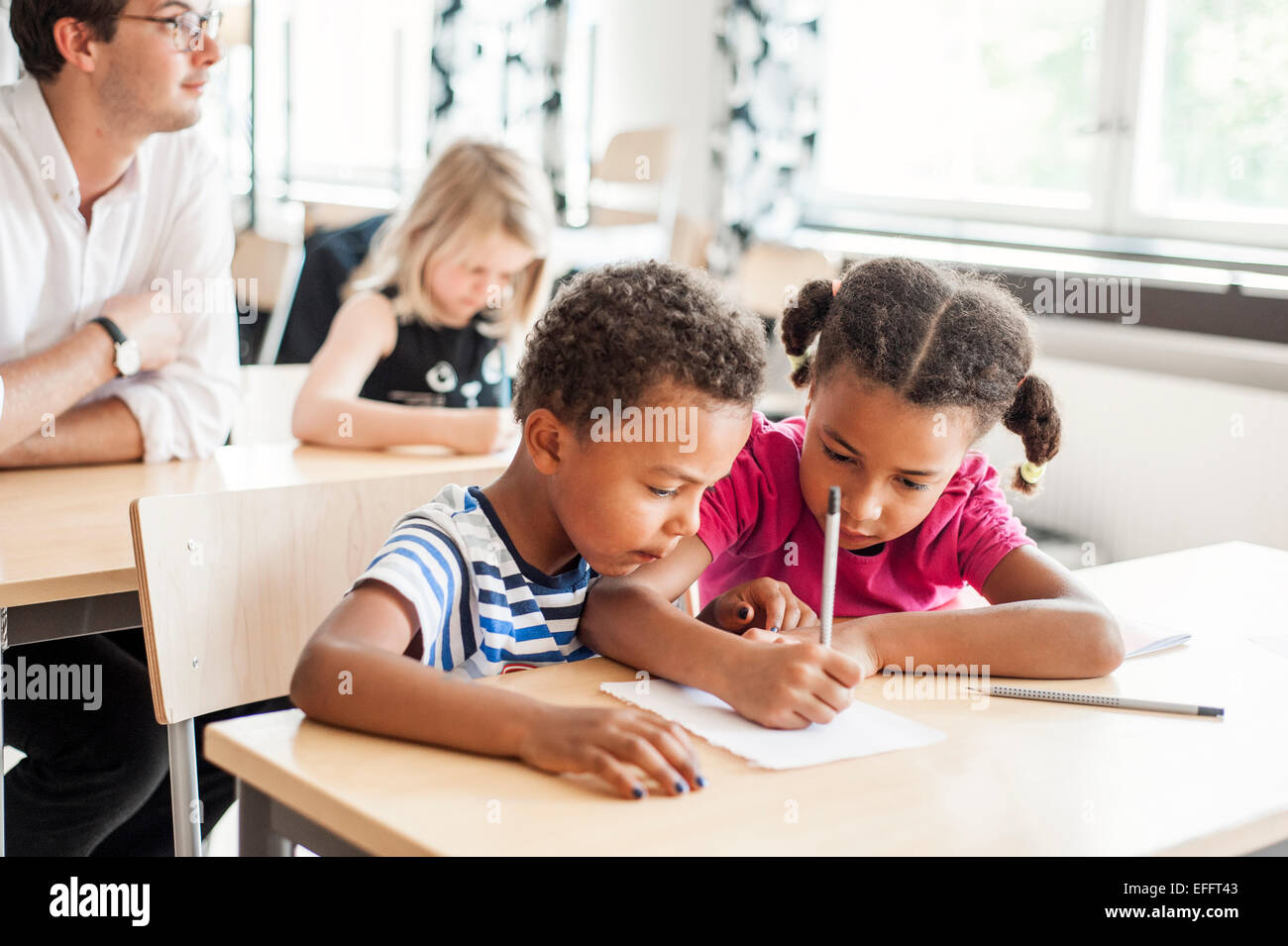 Children studying in classroom - Stock Image