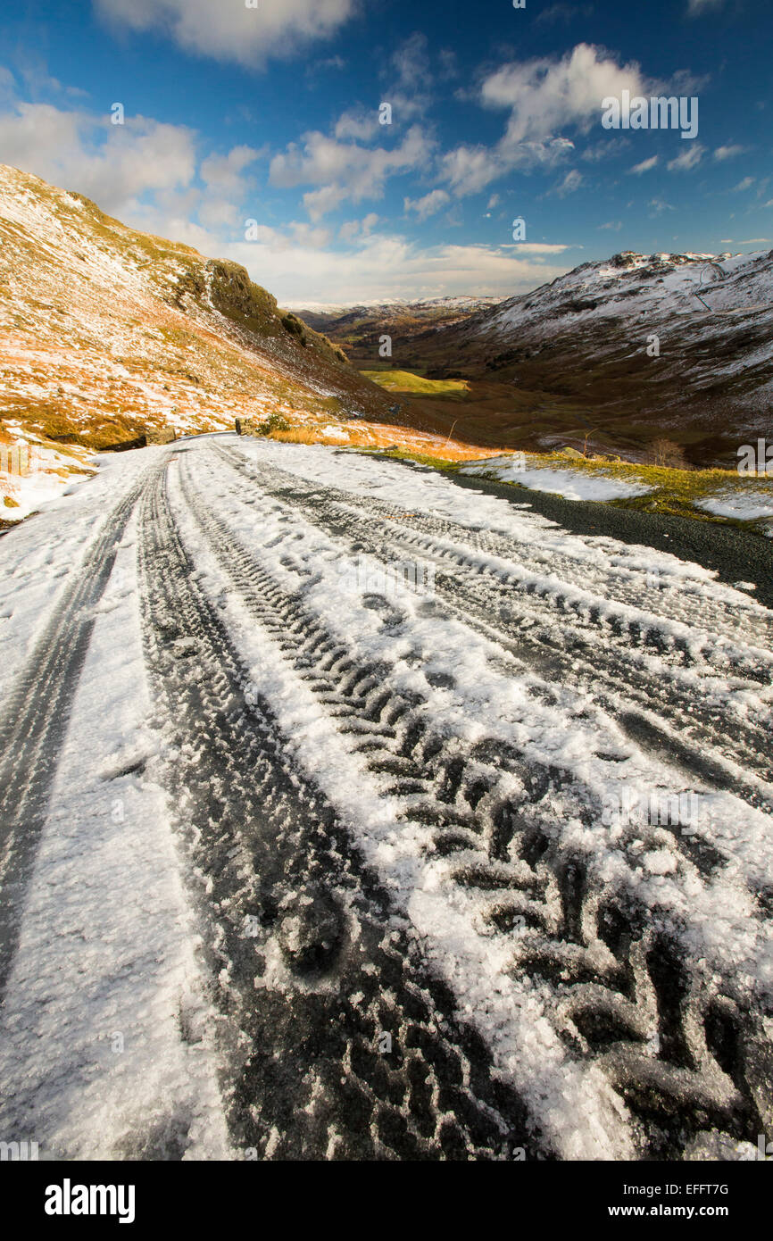 Tyre tracks on Wrynose Pass in winter, Lake District, UK. - Stock Image