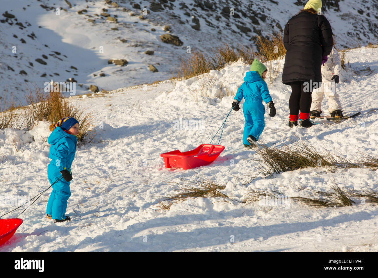 A family sledging on Kirkstone Pass in the Lake District, UK. - Stock Image