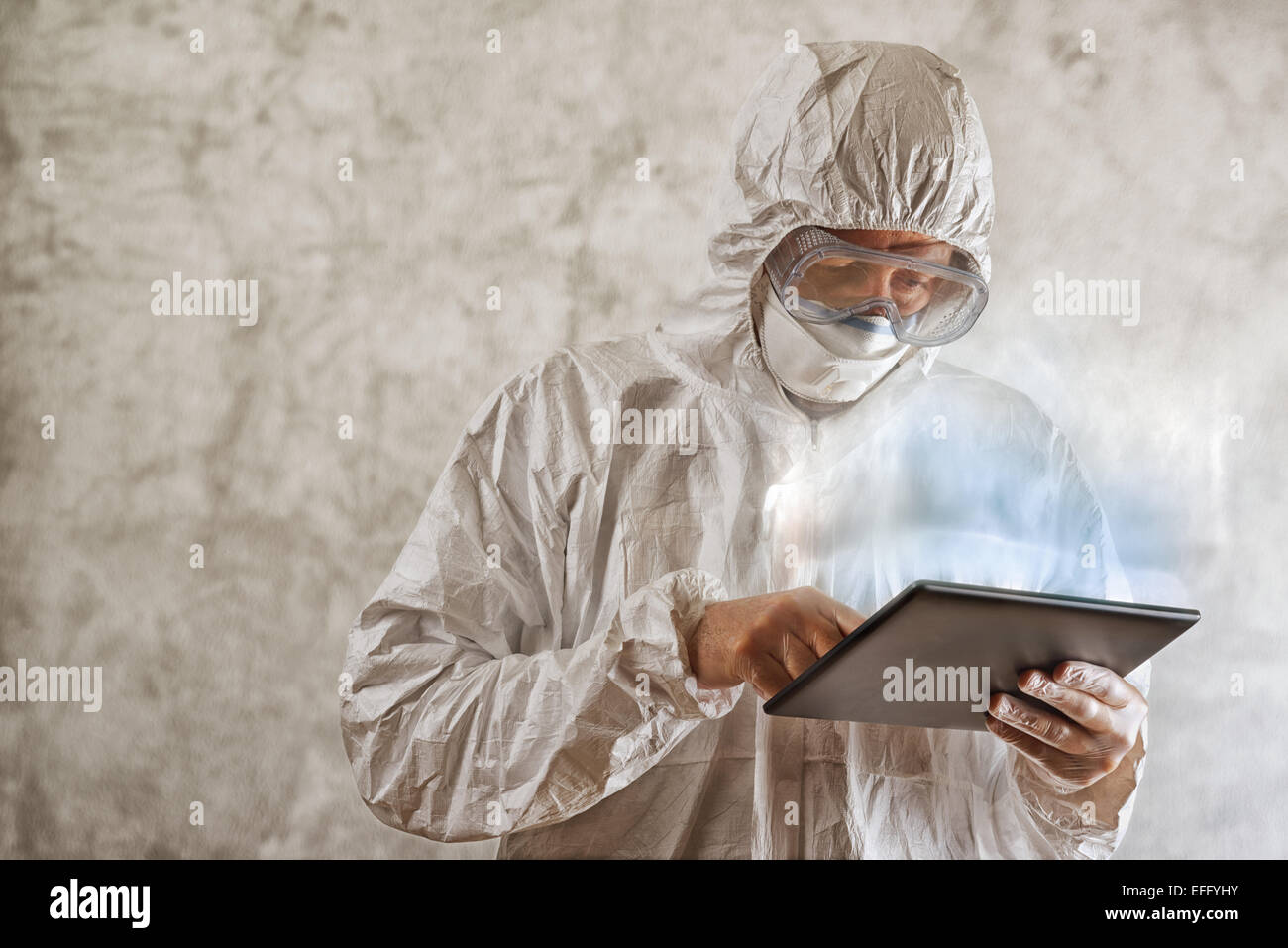 Chemical Scientist in Protective Laboratory Clothing Using Digital Tablet Computer - Stock Image