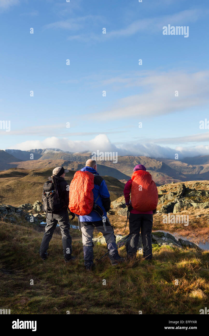 Hill Walkers on Satura Crag Enjoying the Spectacle of Cloud Spilling Over Helvellyn and the Dodds Lake District - Stock Image