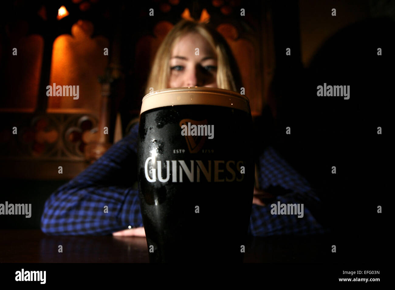 A woman with a pint of Guinness beer - Stock Image