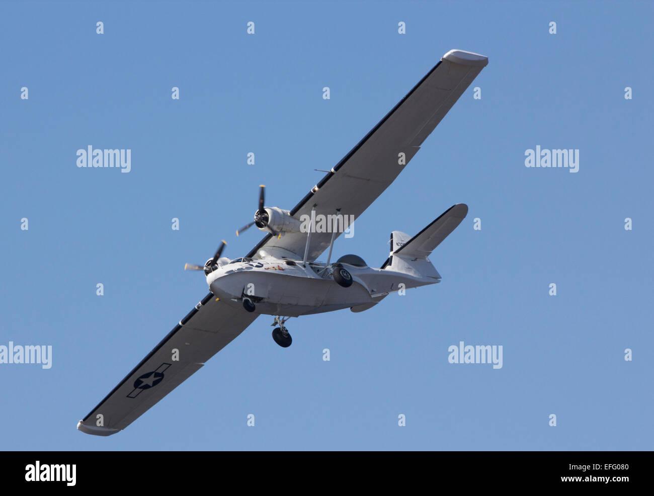 A World War 2 era Catalina flying boat in flight. It has its landing gear deployed - Stock Image