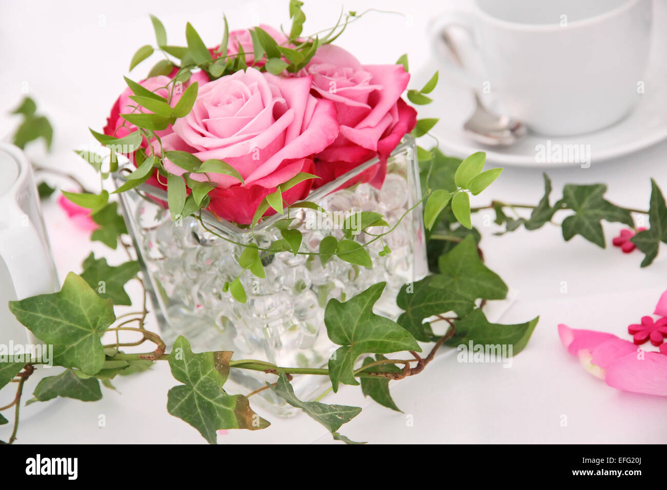Solemnly laid table for a wedding with white and pink - Stock Image