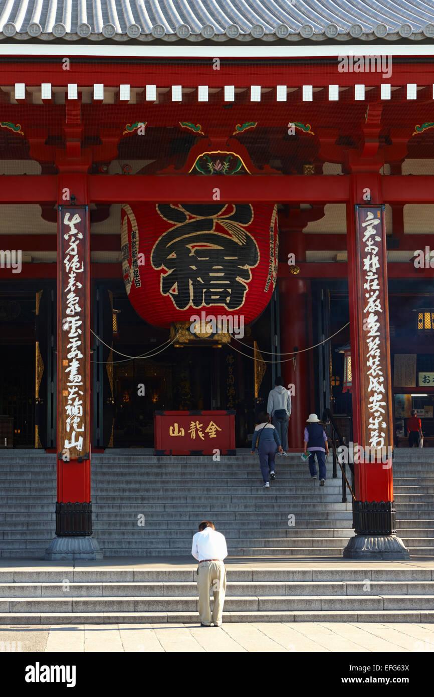 Man bowing in front of Kannon Hall, Senso-Ji Temple, Asakusa, Tokyo, Japan - Stock Image