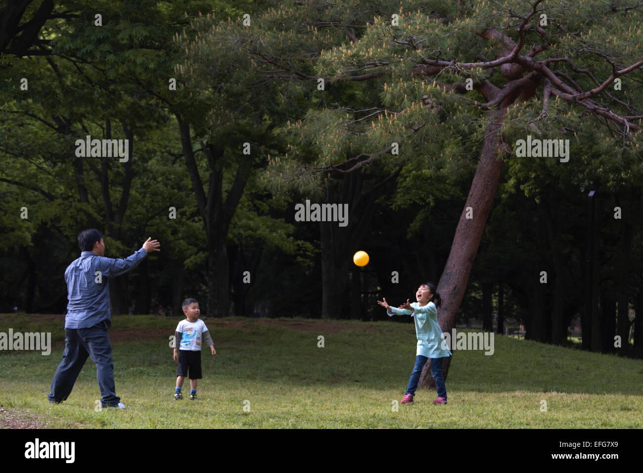 Man and children playing catch in Yoyogi park, Harajuku, Tokyo, Japan - Stock Image