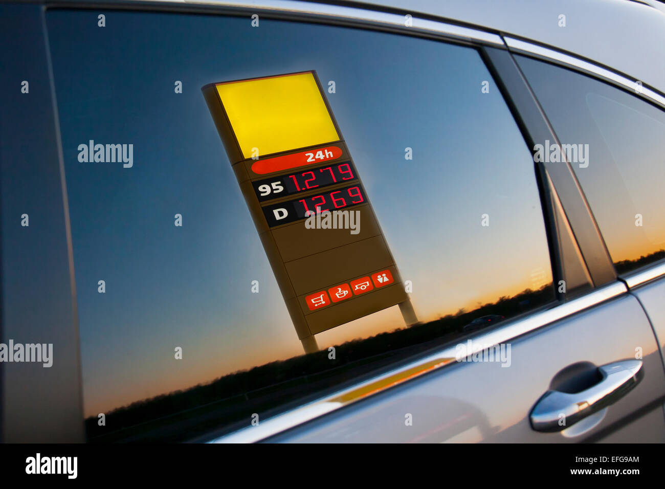 Gas, petrol station price post refection on car side glass. Door, closeup. - Stock Image