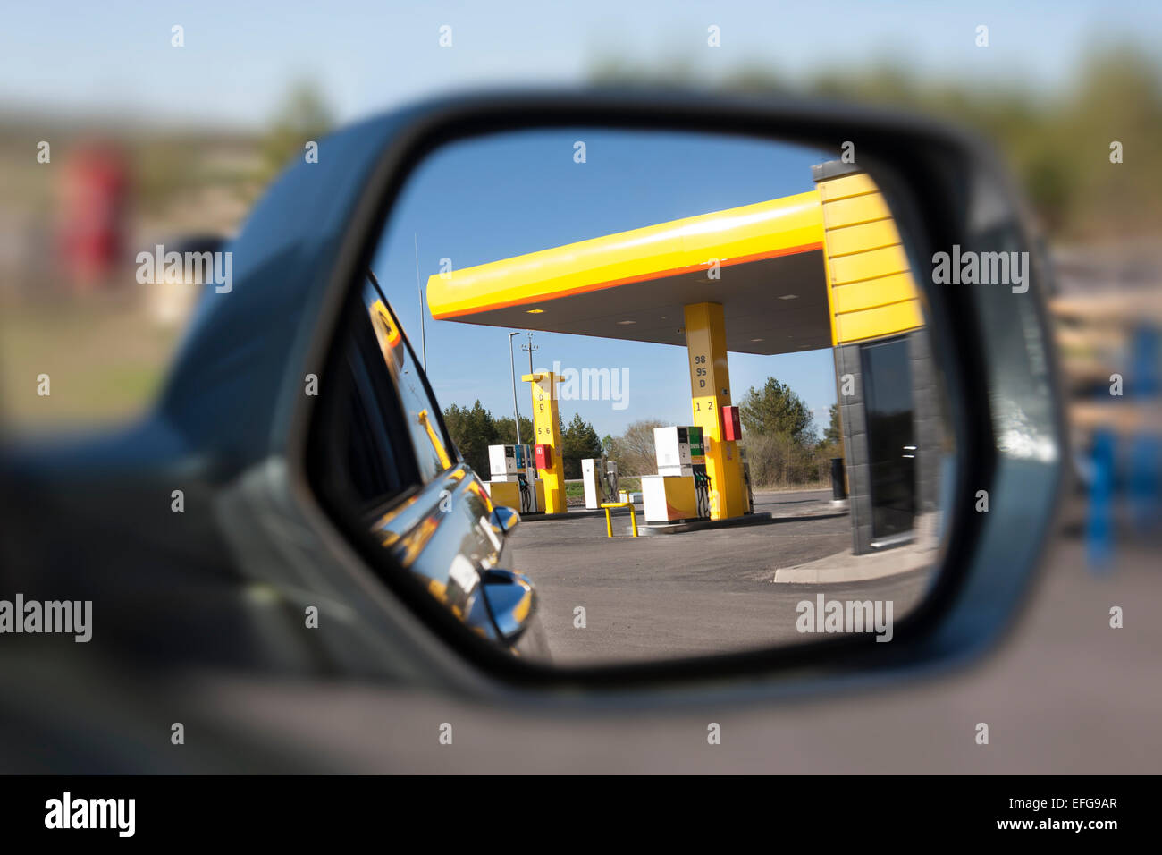 Reflection of gas station on vehicle side mirror. Selective focus. Petrol station with dispenser and pumps. - Stock Image
