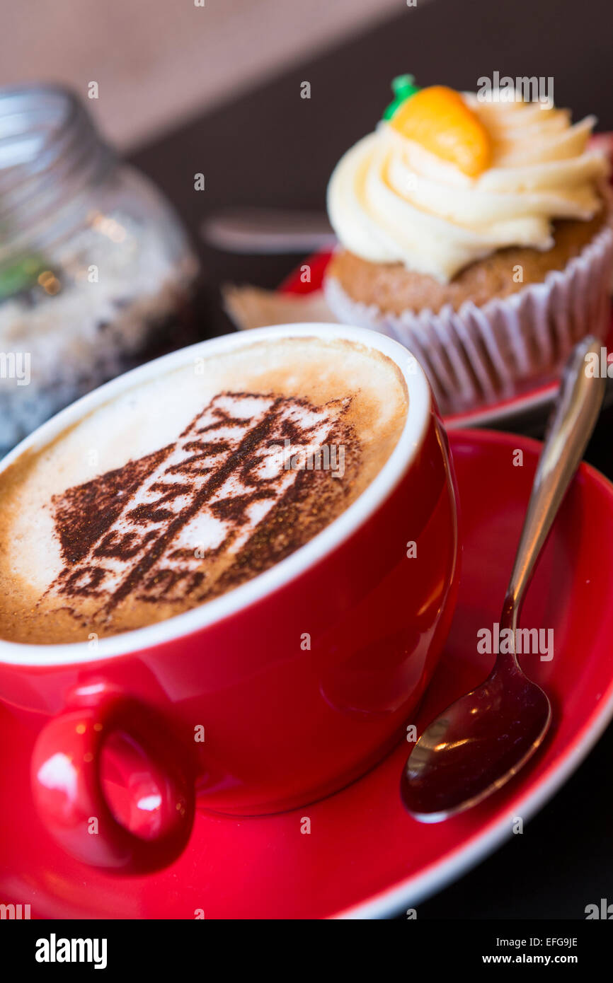 A cup of coffee with a  logo of Penny Black and a carrot cupcake taken in The Penny Black Cafe and Post Office on - Stock Image