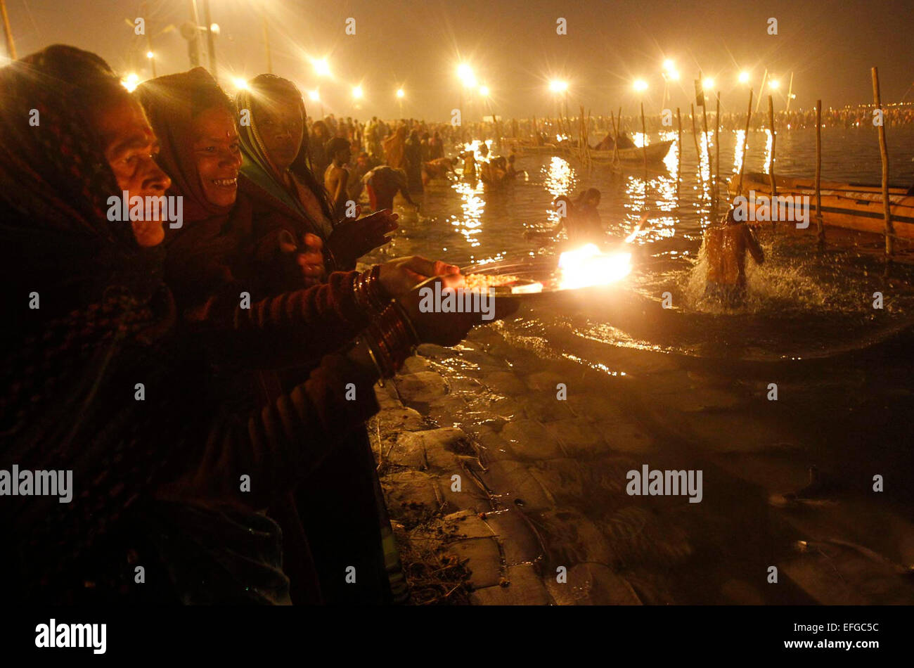 Pilgrims offer prayer after taking holy bath in the Sangam confluence of three rivers the Ganga, the Yamuna and Stock Photo