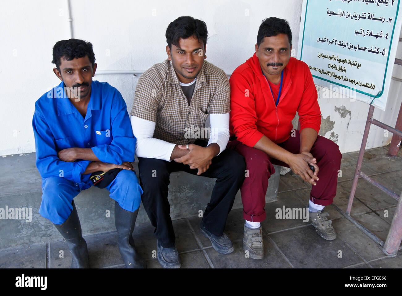 Immigrant workers (from Bangladesh) at Dibba Muhallab fish market, Fujairah, United Arab Emirates - Stock Image