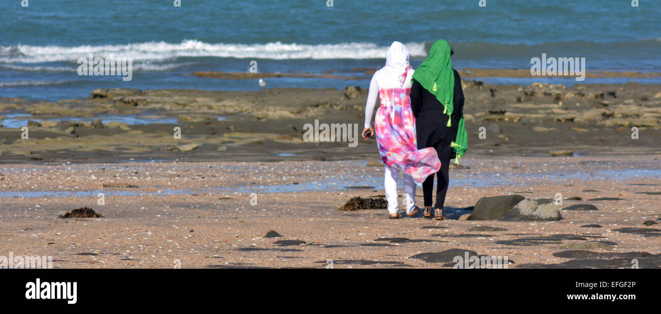 AUCKLAND, NZL - JAN 25 2015:Two muslim women on the beach.Over 130 million women and girls have experienced Female - Stock Image