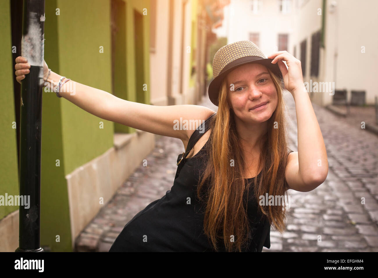 Cute teen girl on the street of old European city. - Stock Image