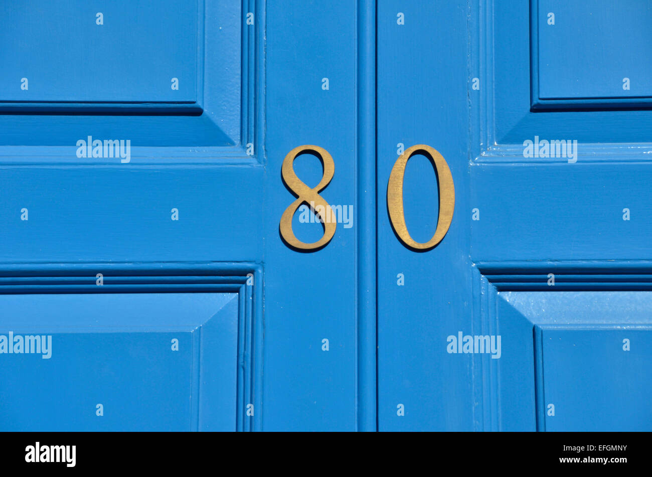 The number 80 on a blue wooden door - Stock Image