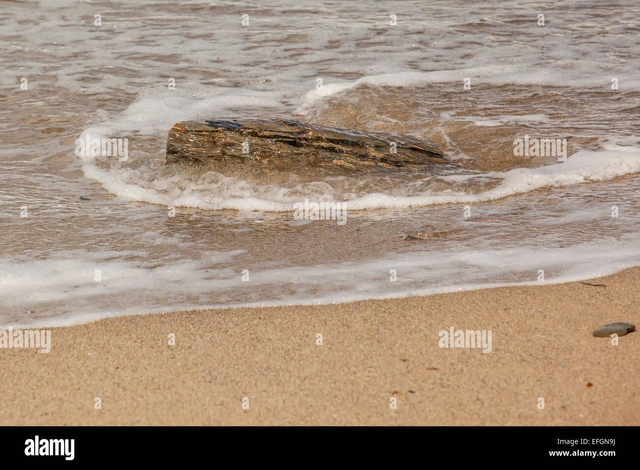 Sea lapping around rock - Stock Image