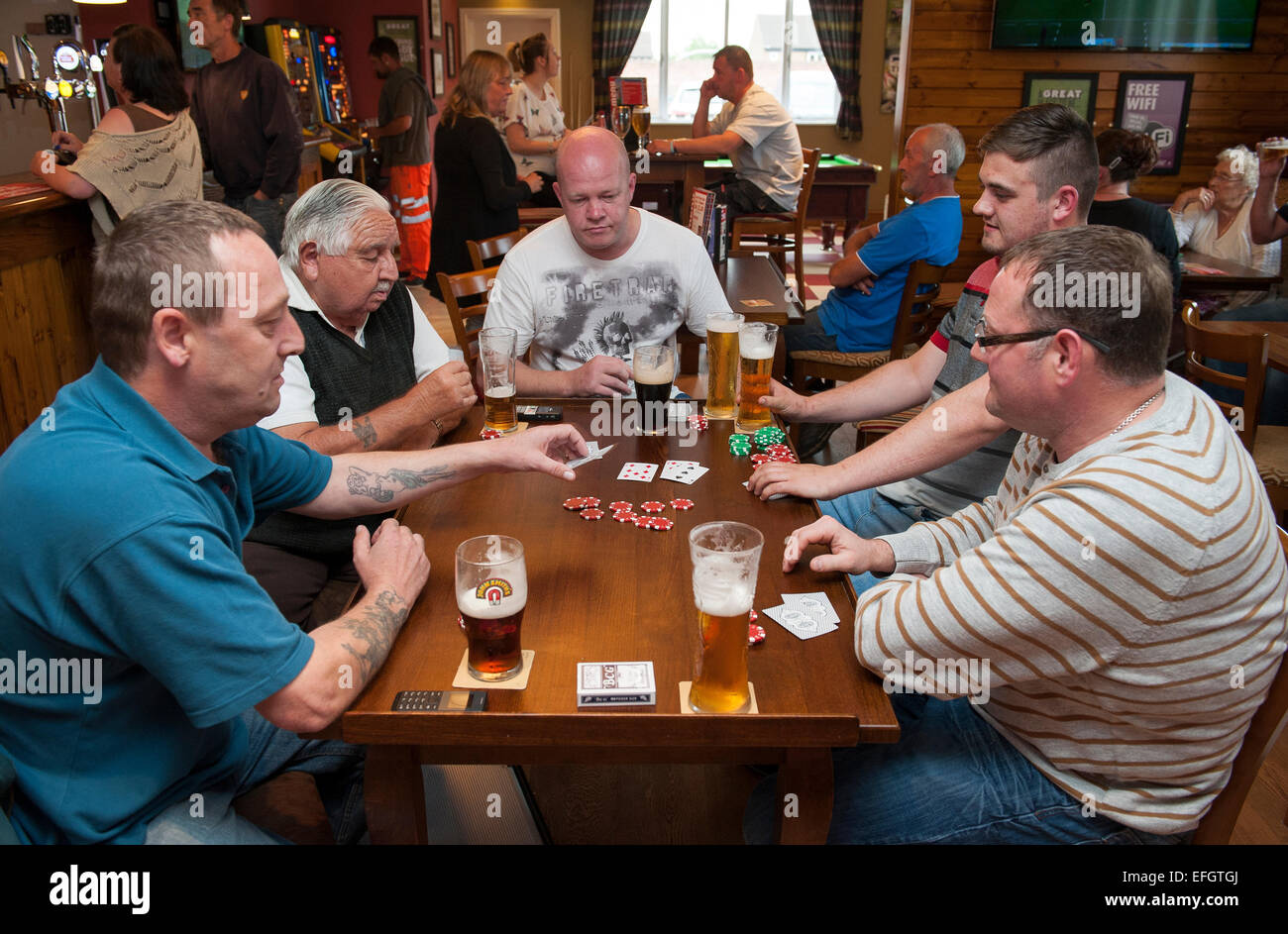 Five men play cards sat around a table in a pub in the North of England while having a drink of beer. - Stock Image