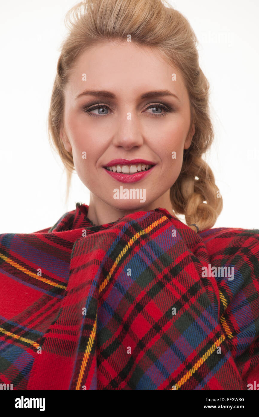 blonde woman wearing a red tartan shawl wrapped around her - Stock Image