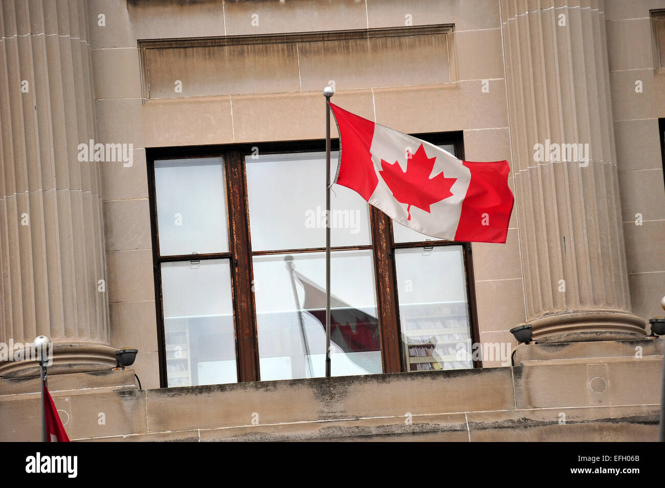 The Canadian flag on a flagpole on the side of a building in London, Ontario, Canada. - Stock Image