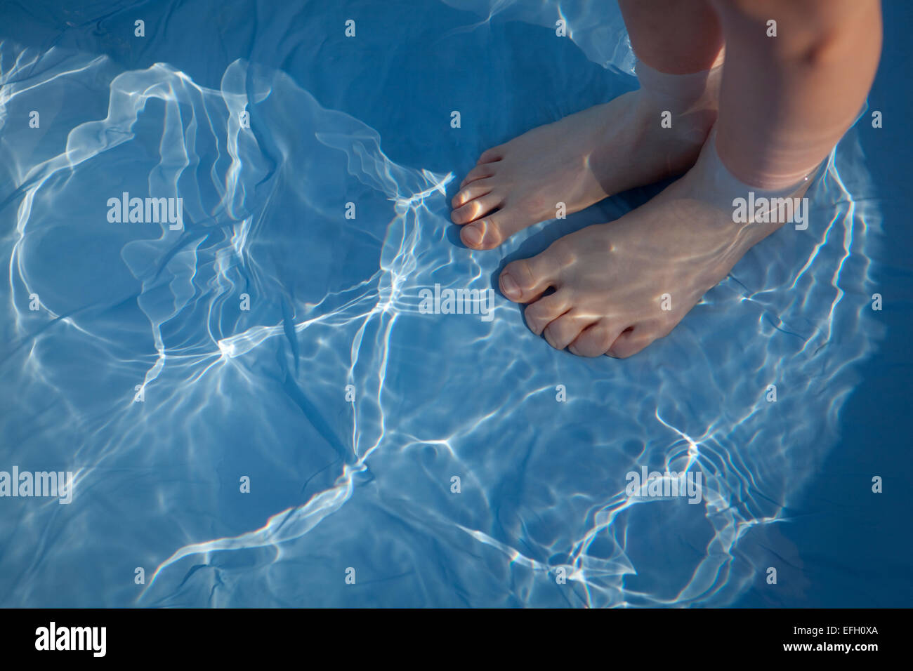 Child's feet distorted under the clear blue water of a paddling pool. - Stock Image